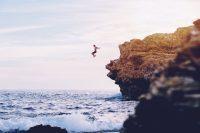 team improvement, man jumping off cliff